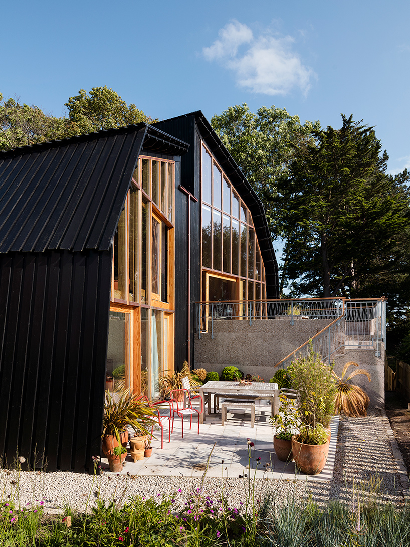 Black stained timber larch boards sit above an exposed concrete base