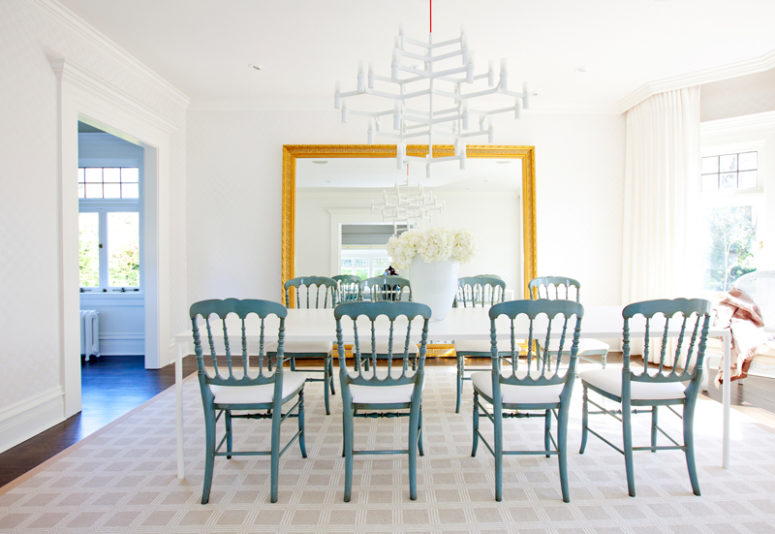 The dining room is spruced up with vintage blue chairs and an oversized gilded frame mirror to make it refined