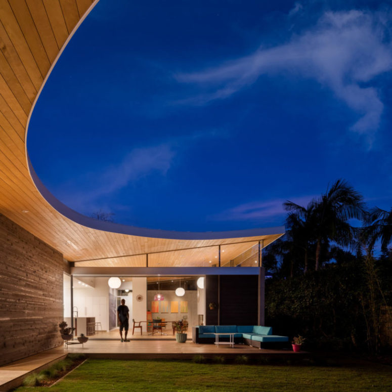 The house is made of three pavilions under one sloping roof, which extends outside to make the house merge with nature