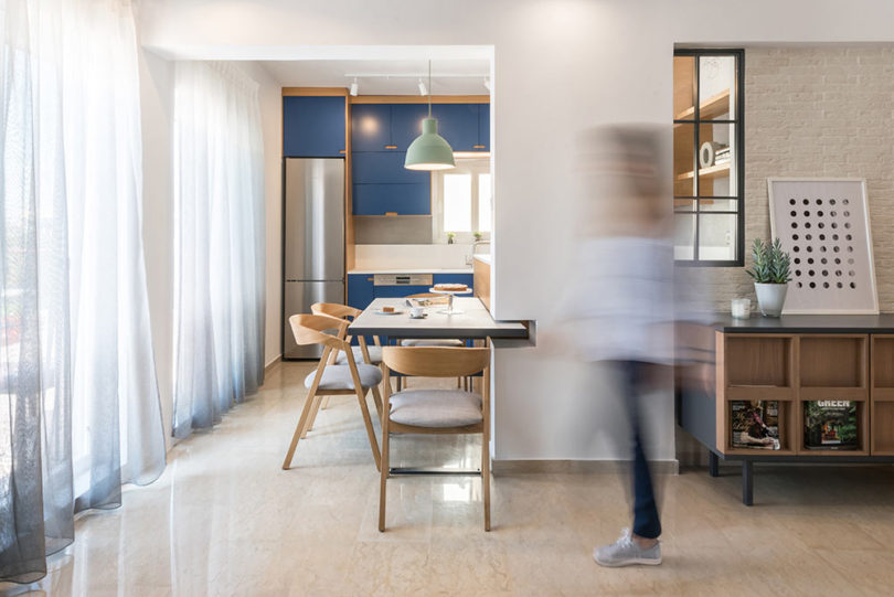 The kitchen is blue, the eating zone is integreated into a kitchen island, which extends to the living room