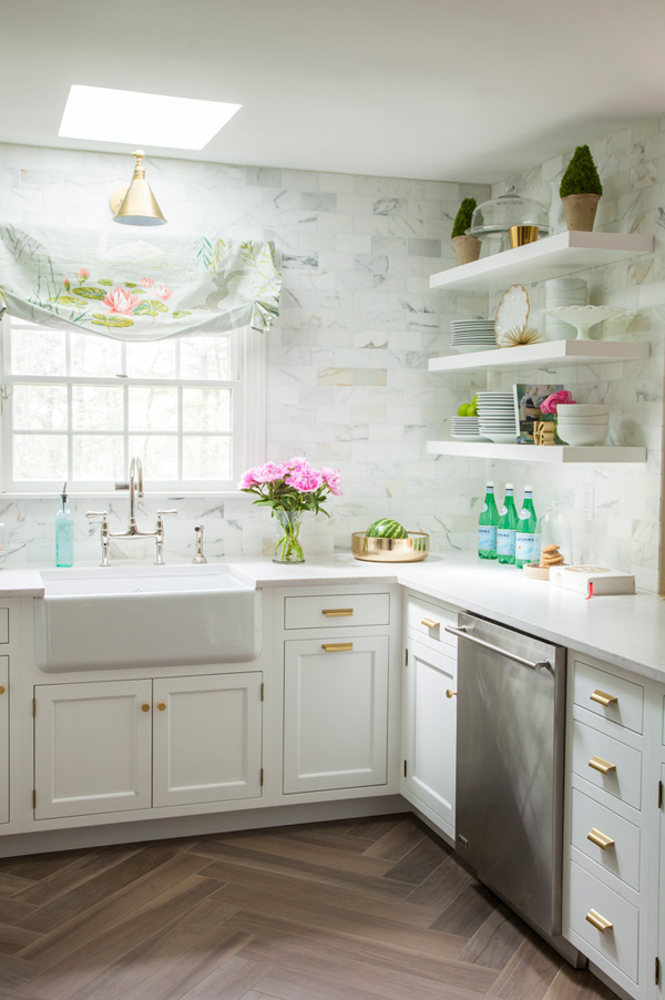 The walls are clad with marble subway tiles, there are white cabinets and floating shelves for comfortable and airy storage
