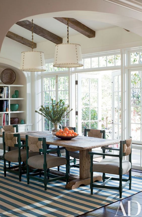 a coastal dining room with a rough wooden trestle dining table that adds texture and style