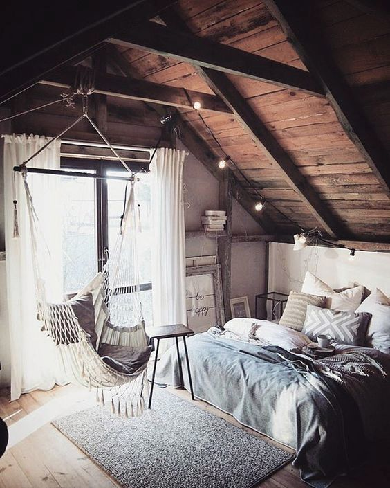 a cozy she shed with a comfy bed, a hanging hammock chair and string lights is perfect for having a rest