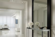 02 oversized wall mirror in a black frame defines the white entryway