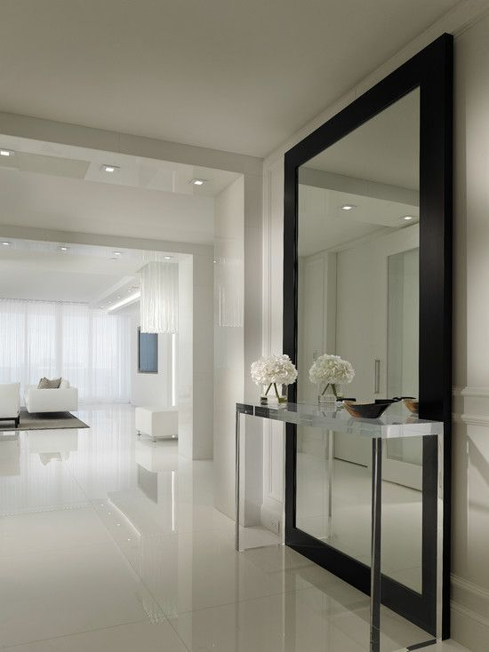 oversized wall mirror in a black frame defines the white entryway