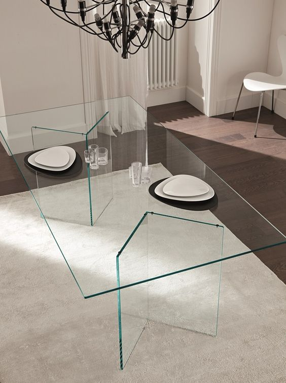 ultra-minimalist dining table with geo glass legs and a glass tabletop, the dishes seem to be floating in the air