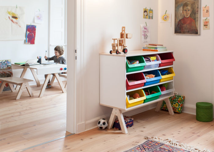 Creative and comfy in using shelving unit with plastic crates that can be removed and used throughout the room