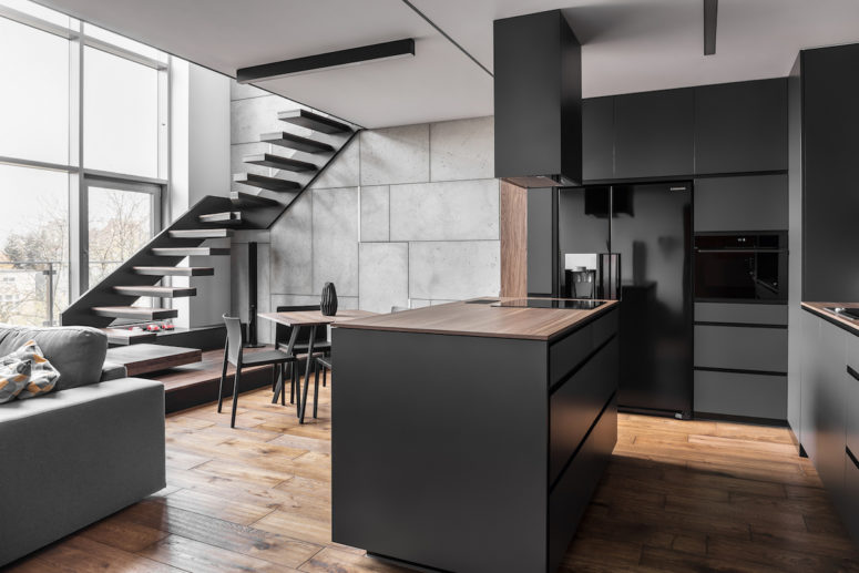 The kitchen is done in matte black and grey, large windows fill the open layout with light, and a linear staircase leaves some space for an eating zone