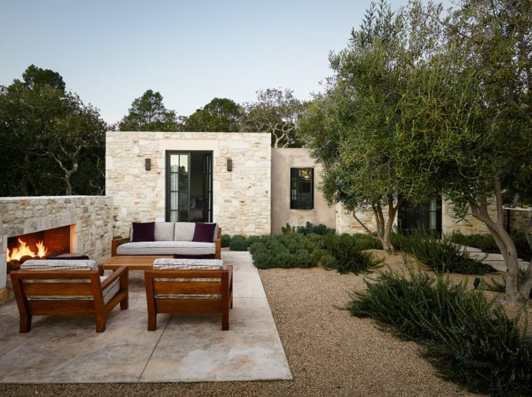 There are two volumes, which are connected with the outdoor space that features a stone fireplace and a sitting space