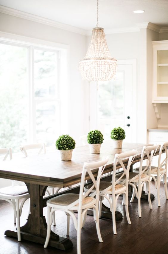 a cottage dining room with white chairs and a wooden trestle table, a glam chandelier to add style to the space