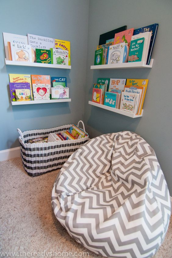 a cozy reading space with a bean bag chair, bookshelves and a basket to encourage reading