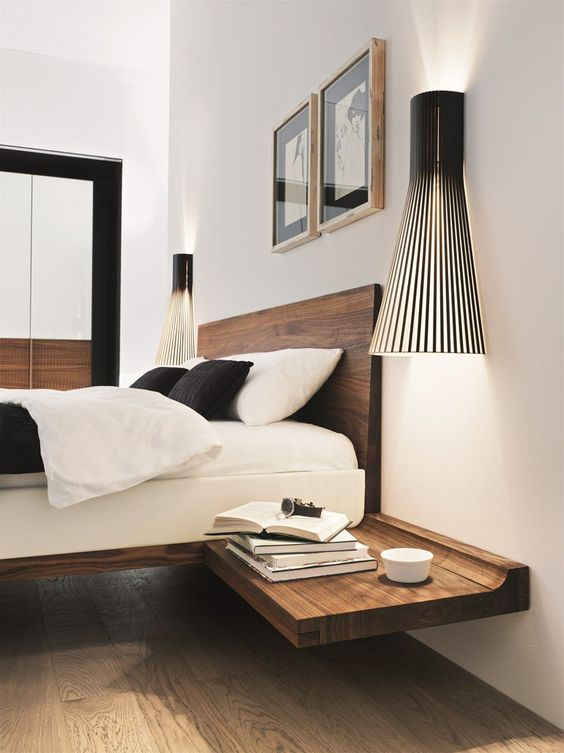 a floating wooden nightstand attached to the bed frame and in a matching shade