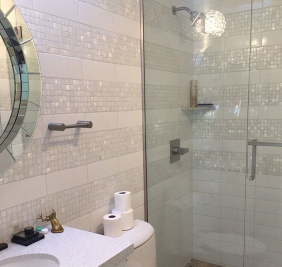 a glam creamy bathroom with mother of pearl accents and a mirror for an ambience