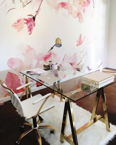 a glam trestle desk with brass legs and a glass tabletop and a matching brass and