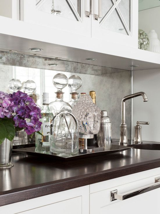 a silver faded mirror backsplash in easily maintainable and looks nice with white cabinets