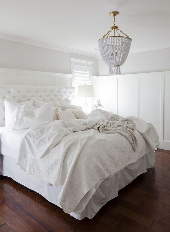 a textural bedspread and a diamond upholstery headboard add eye-catchiness to this light-filled bedroom