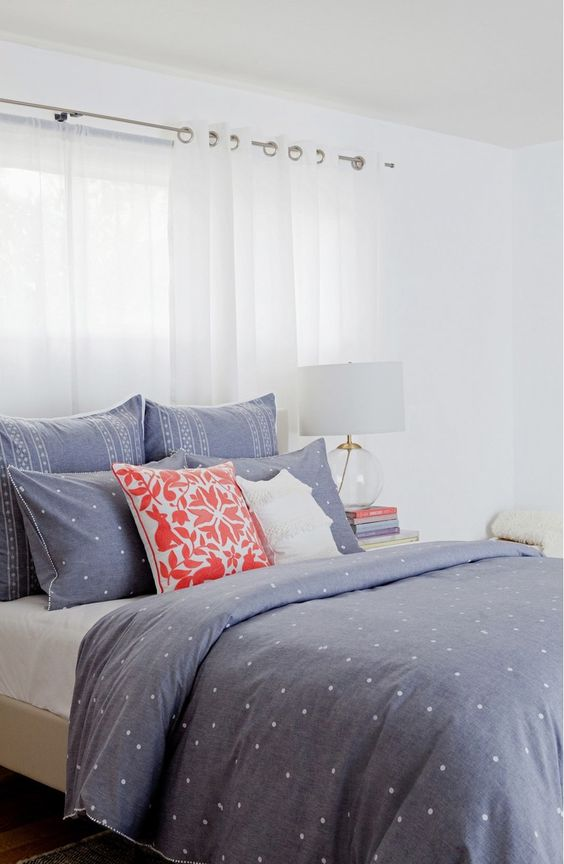 blue and white polka dot bedding set with other prints and two acent pillows in white and coral