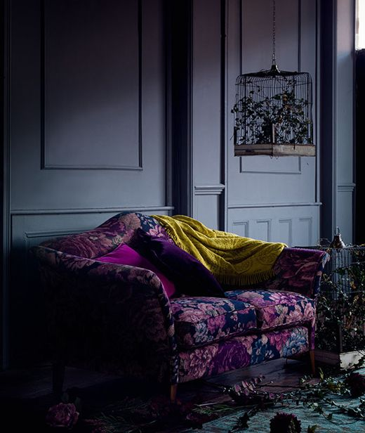 if your space is moody and dark, why not go for a deep purple and blue loveseat that fits the style