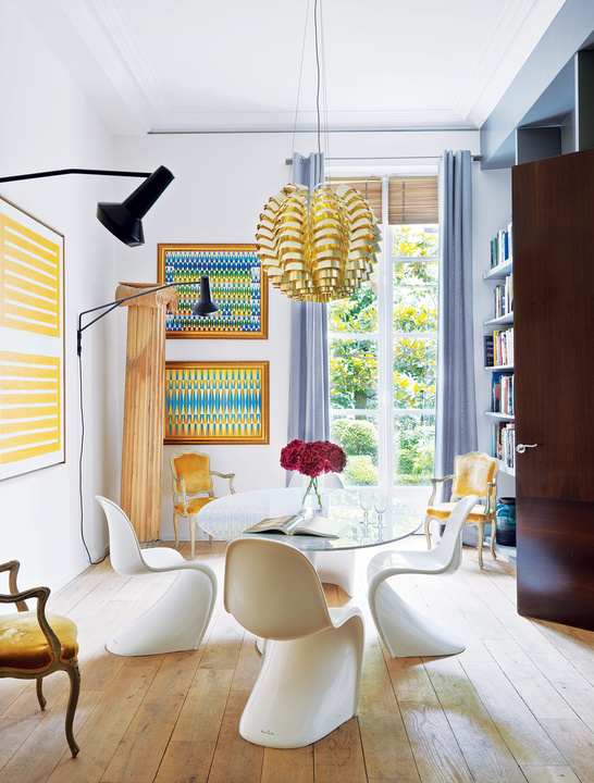 The dining room is accentuated with sunny yellow and blue, look how Pantone chairs fit the glass top dining table - this is a gorgeous idea