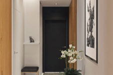 04 The floor in the entryway is marble, it looks fresh, refined and is durable, and a tall modern planter with beautiful flowers make the space refined