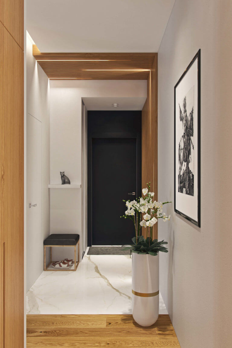 The floor in the entryway is marble, it looks fresh, refined and is durable, and a tall modern planter with beautiful flowers make the space refined