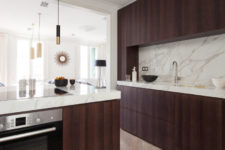 04 The kitchen features dark stained wooden cabinets and luxurious white marble countertops and a backsplash
