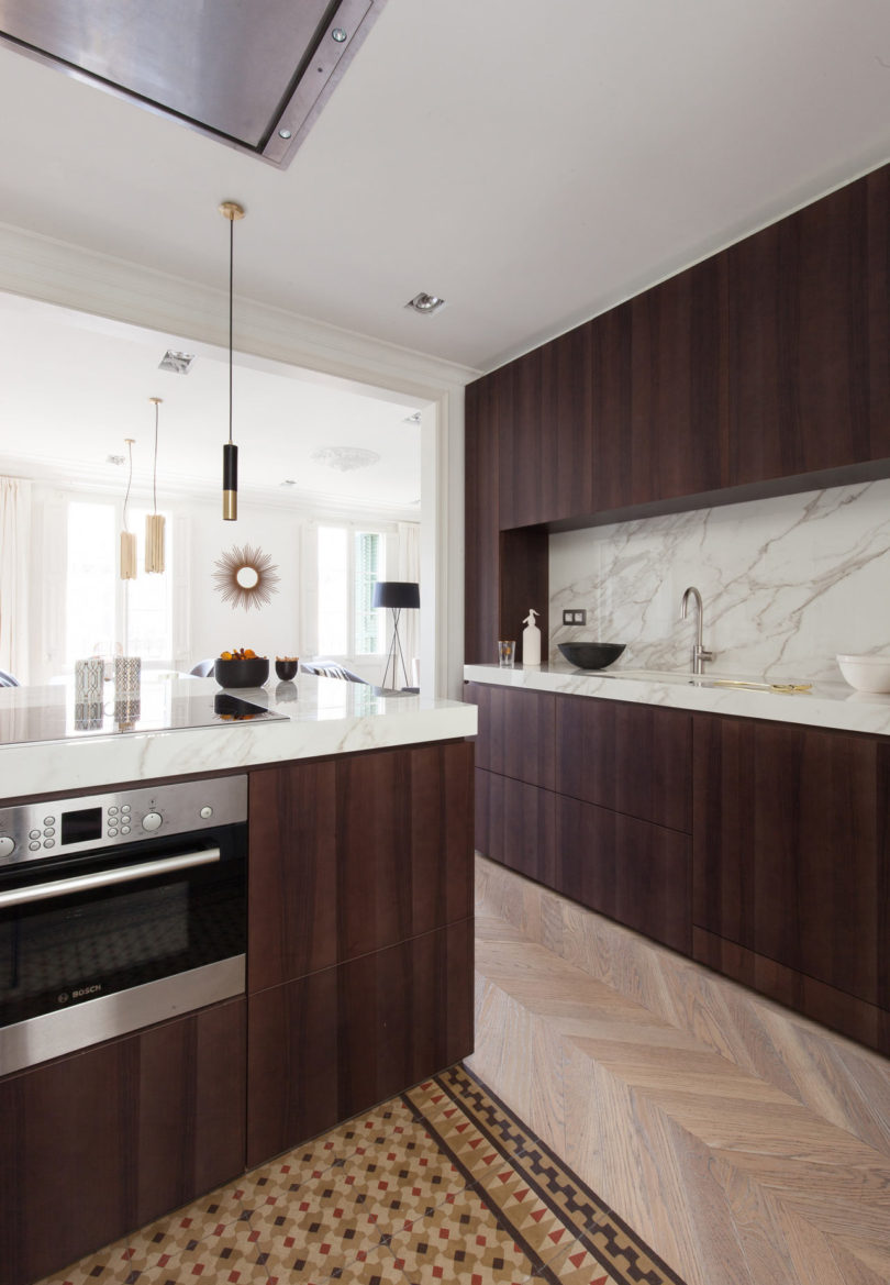 The kitchen features dark stained wooden cabinets and luxurious white marble countertops and a backsplash