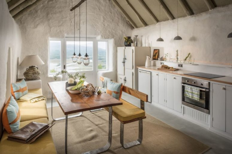 The kitchen is a line of cabinets by the wall, and the dining zone offers amazing views on the landscape