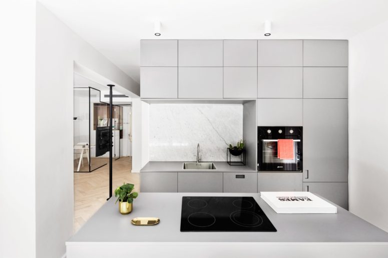 The kitchen is modern and minimalist, it's done in light grey with marble inserts and some brass touches for elegance
