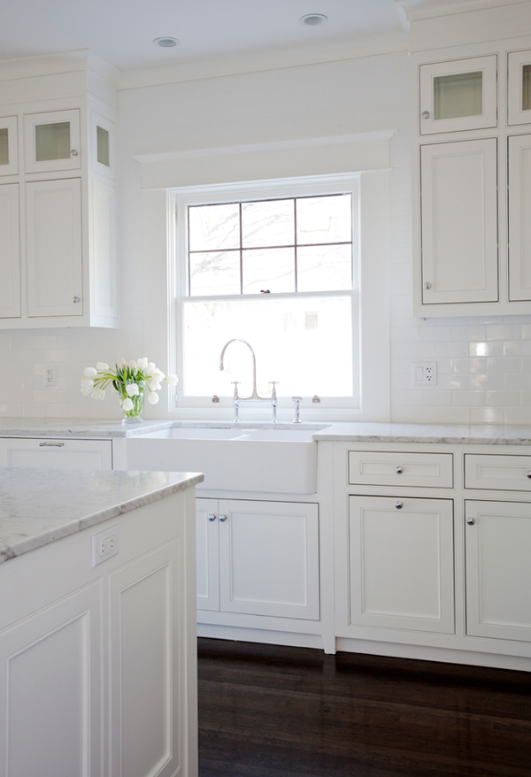 The kitchen is traditional and all-white, white marble countertops add a chic touch to the space