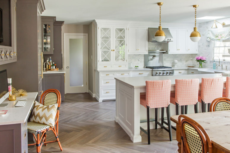 The kitchen island is large and doubles as a breakfast zone, the space is spruced up with peachy chairs