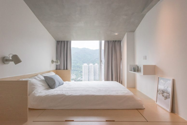 The master bedroom looks peaceful, with a concrete ceiling, adorable views and a bed on a platform