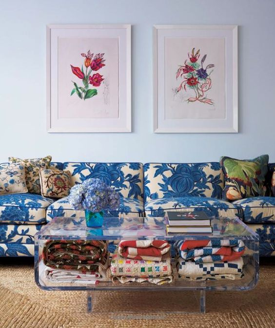 a blue floral print sofa contasts a modern Lucite coffee table