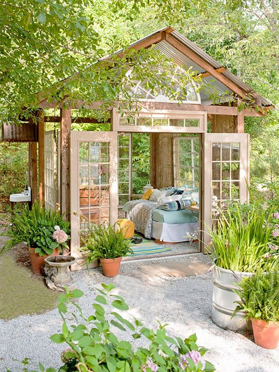 a glass she shed with a daybed and aqua and turquoise colors in decor to enjoy sunlight