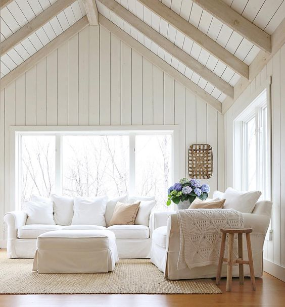 a neutral living room is made cooler with whitewashed wooden planks that cover the ceiling and different textiles