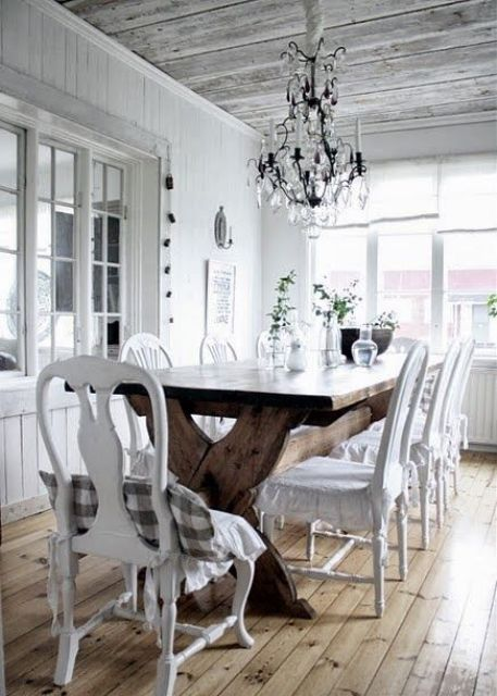 a white shabby chic dining space with a wooden trestle table