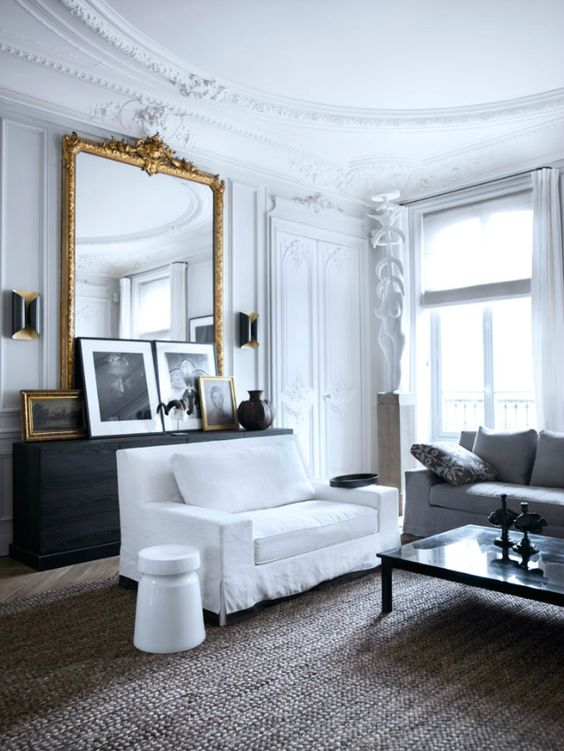 an antique French framed mirror adds chic and beauty to this living room