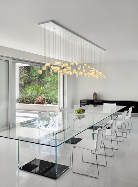 an ethereal all-glass dining table with dark bases and neutral chairs, a pendant lighting fixture to accentuate the space