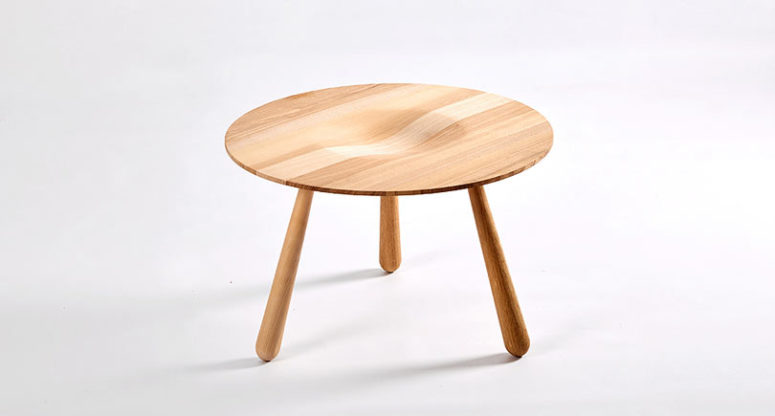 A wooden coffee table with a texture and a curved tabletop