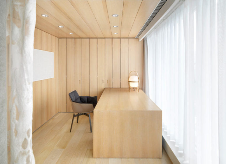 The home office is very laconic, all clad with wood and with a desk of the same type of wood