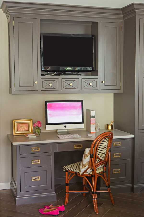 The home office is visually divided from the kitchen with a different shade of cabinets and more traditional design