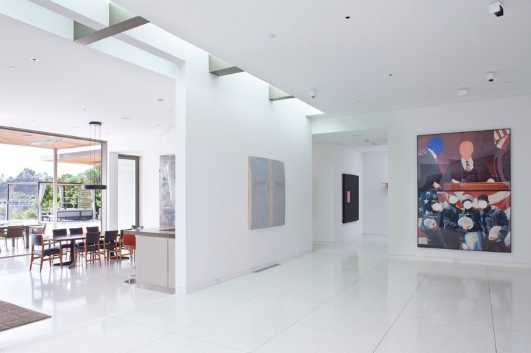 The interior spaces are done in white to feature a perfect backdrop for the owner's art collection and a simple material palette is characteristic of modernist style