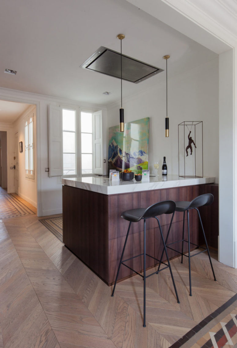 The kitchen island doubles as a breakfast zone or a home bar when needed
