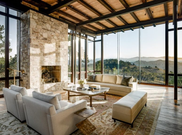 The living room is made with a stone fireplace and there's cozy cream upholstered furniture and glazings offer amazing views