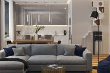 05 The living space features a large grey sofa with navy pillows, and the kitchen comes in the same shade of grey, too