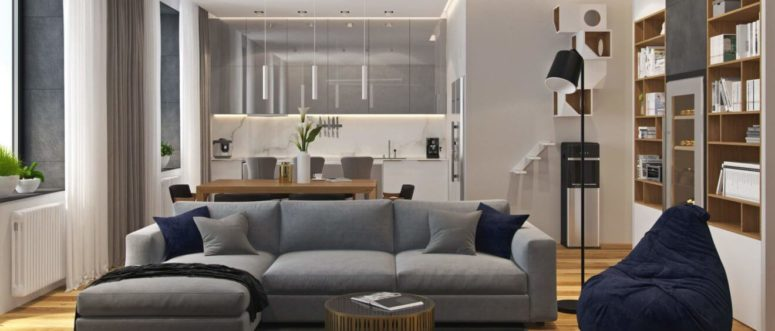 The living space features a large grey sofa with navy pillows, and the kitchen comes in the same shade of grey, too