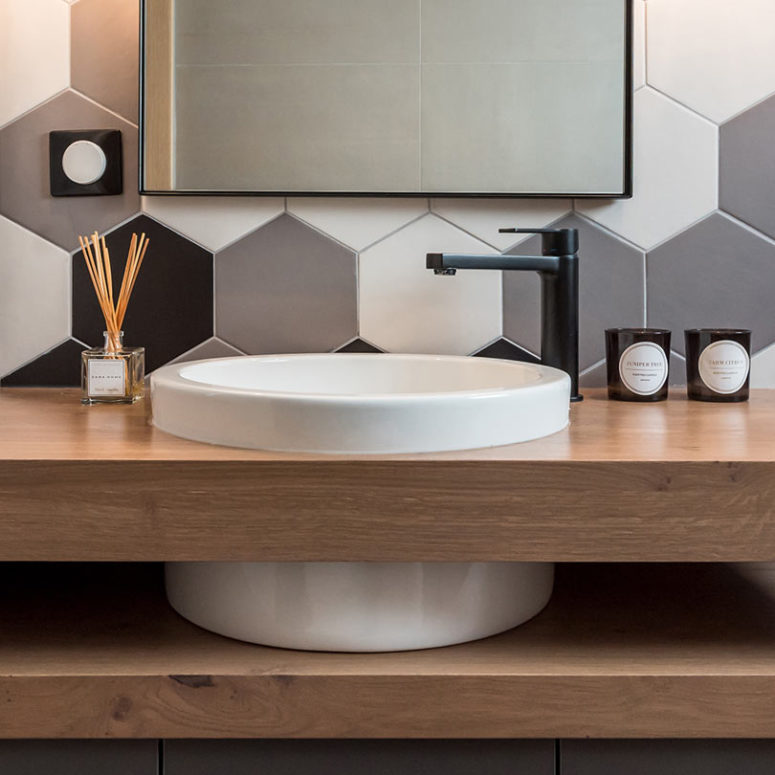 The powder room features a modern round sink in a double wooden vanity and hexagon tiles