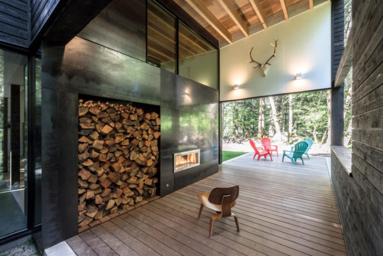 There's a covered outdoor veranda that features a fireplace with firewood storage and a sitting space