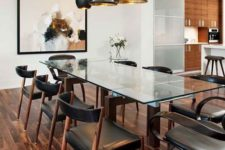 05 a chic modern table with stained wooden legs and a glass top, marching chairs with leather upholstery and black and gold pendant lamps