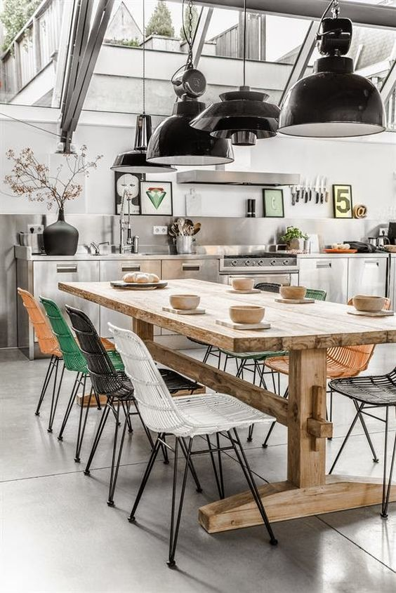 a modern industrial inspired space with colorful chairs is made warmer with a wooden table